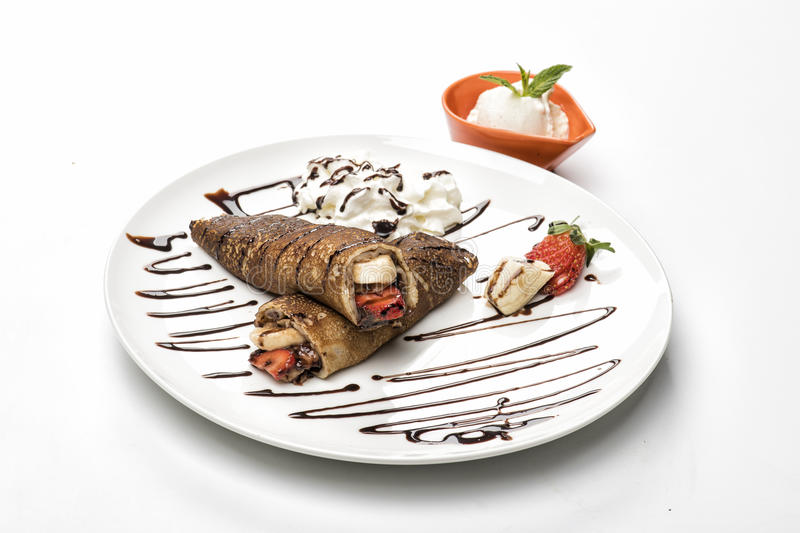 Two folded crepes with strawberries. Cream and chocolate sauce, isolated on white royalty free stock images