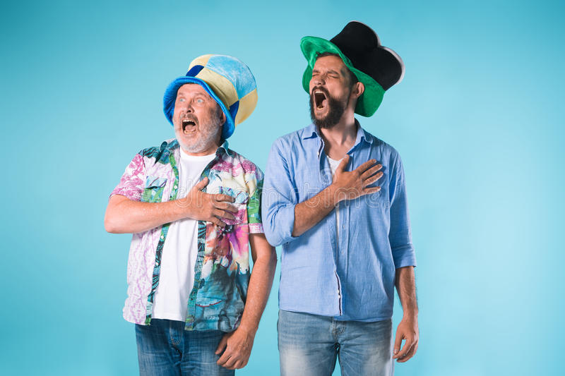 The two football fans singing the national anthem over blue. Background stock photos