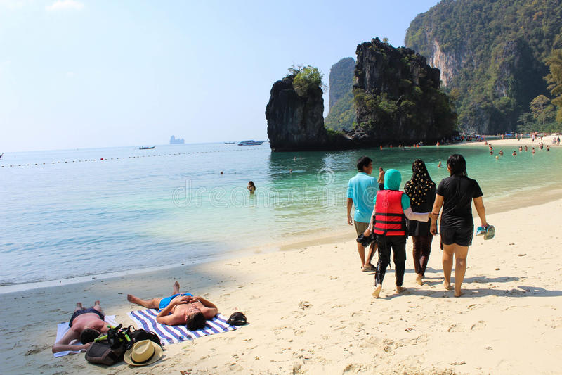 Two foreigners sunbathing and Thai tourist goup walk royalty free stock images