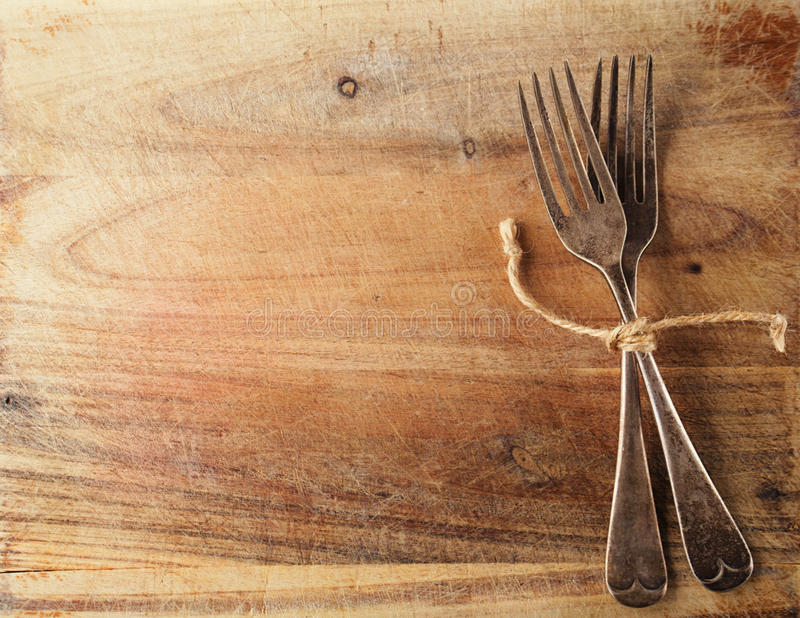 Two fork tied by string on old wood, background stock photo