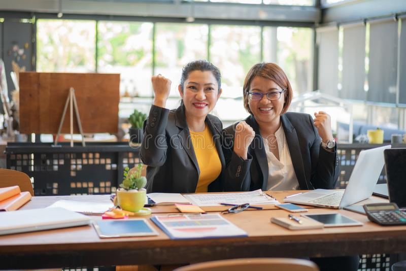 Two freelancer beautiful asian woman happy success business project with digital laptop computer at workplace coffee shop royalty free stock photo