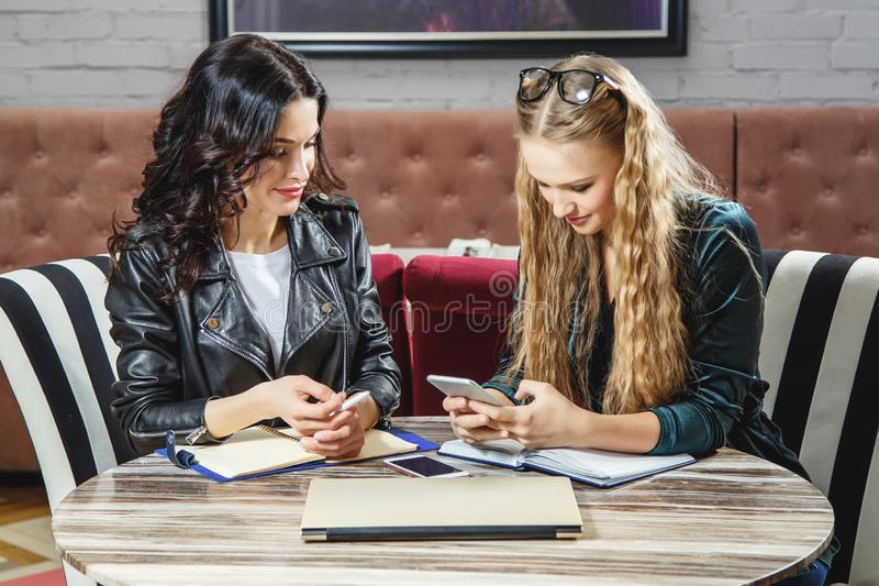 Two freelancers are discussing new projects while sitting in a cafe. Business meeting. royalty free stock image