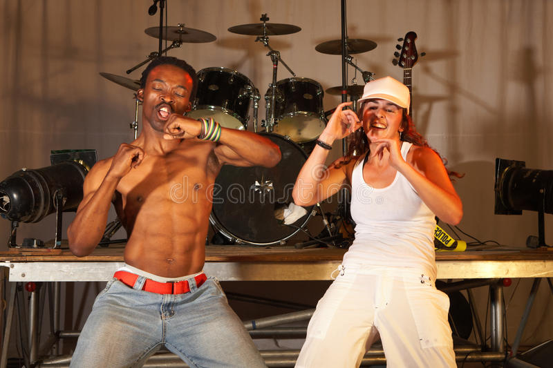Two freestyle hip-hop dancers. A man and a woman at a training session on stage with instruments in the background stock photos