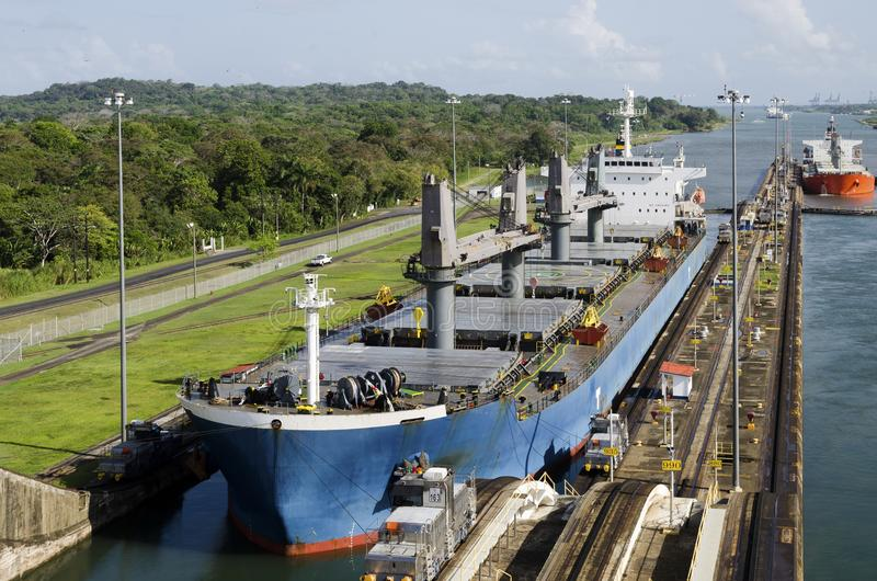 Merchant ships pass the locks of the Panama Canal. stock images
