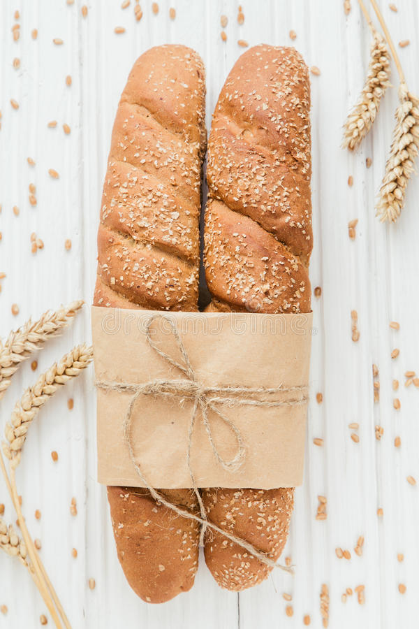 Two French baguettes on white wooden backdrop stock image