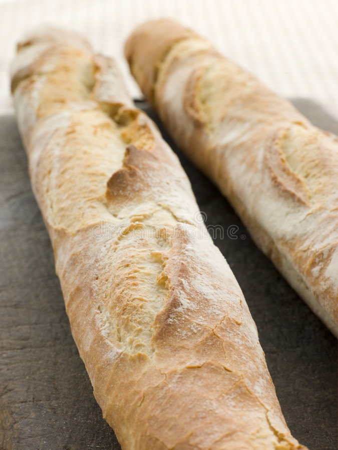 Two French Sticks. On a bread board royalty free stock images
