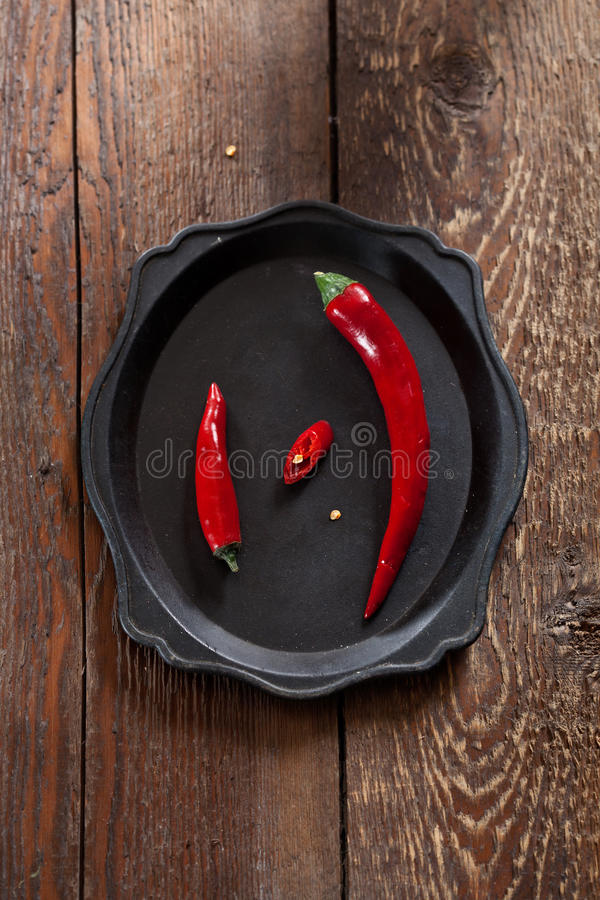 Two fresh chilli peppers, big and small. On an old tray on a wooden board royalty free stock images