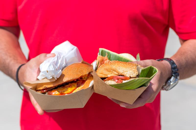 Two fresh delicious grilled burgers in man`s hands. Street food festival royalty free stock photo
