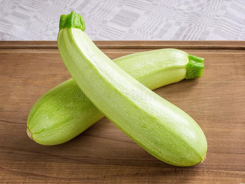 Two fresh green courgettes or zucchini criss-cross on a brown wooden cutting board. Cook at home. Fresh vegetables, vegetarianism royalty free stock photography