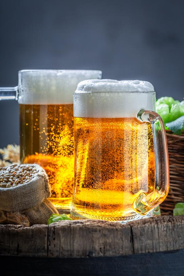 Two fresh light beers on wooden barrel. On dark background stock photography