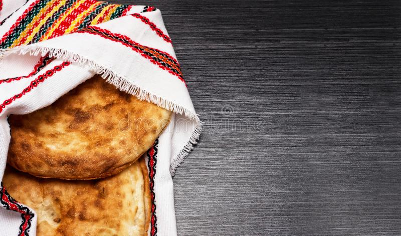Two fresh pita bread covered with festive napkin on wooden table stock photo