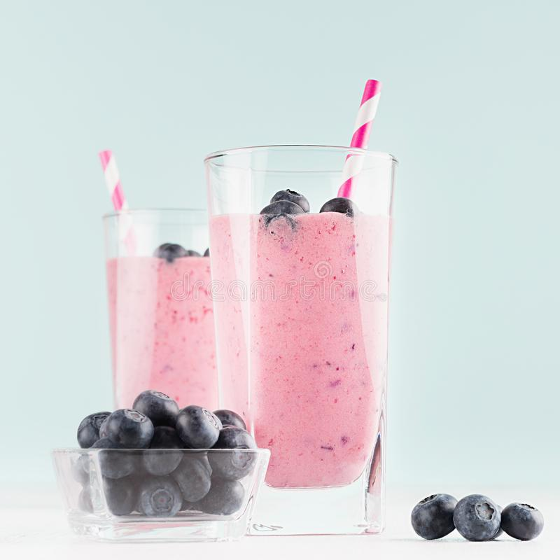 Two fresh purple milkshakes with blueberries in bowl, striped straws closeup on soft light mint color background and white wood. Two fresh purple milkshakes royalty free stock photo