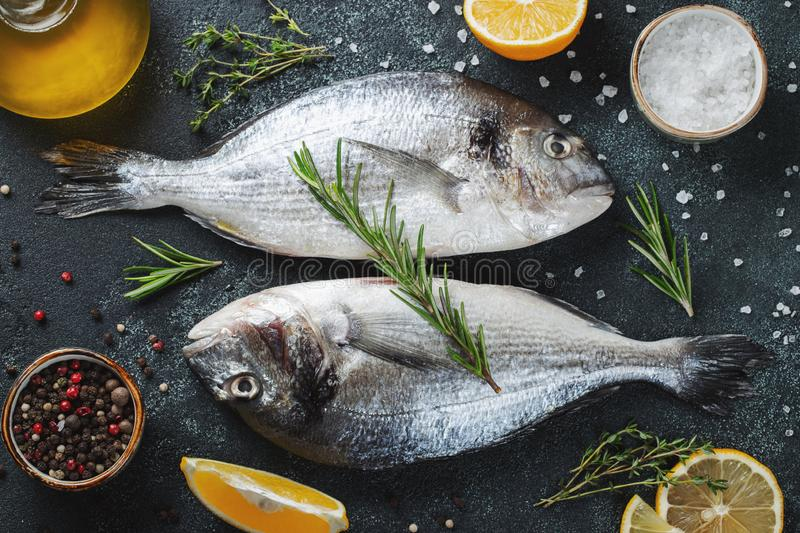 Two fresh raw Dorado fish with spices and olive oil on a dark stone table. Top view. Flat lay.  stock images