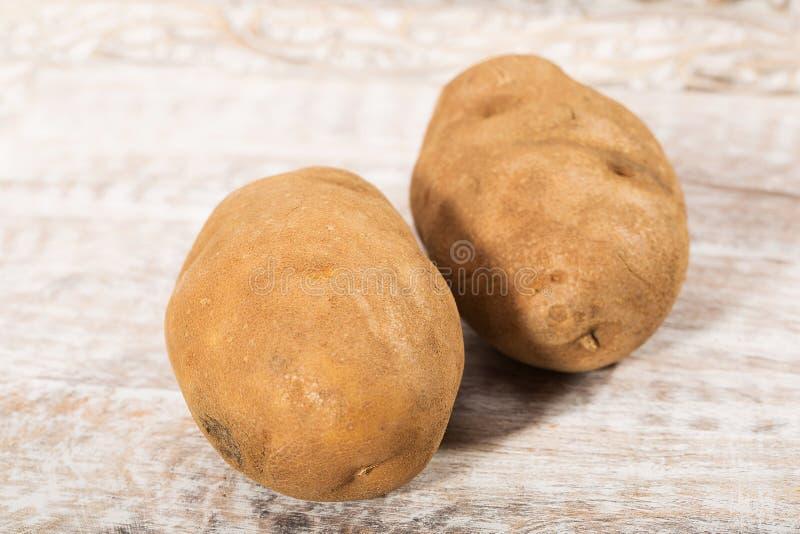 Two fresh, raw potatoes. Two potatoes fresh and raw royalty free stock photos