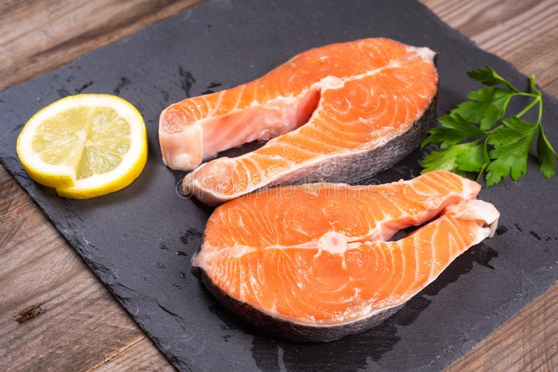 Two fresh raw salmon steaks with lemon and parsley on the rustic table stock photos