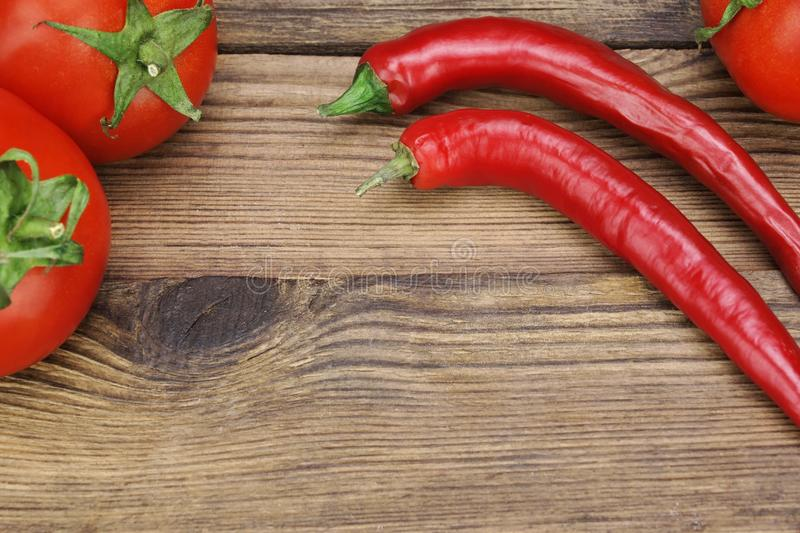 Two Fresh Red Hot Chili Peppers And Tomatoes stock photography