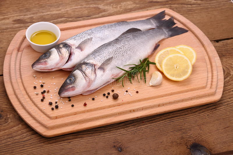 Two fresh sea bass fish on cutting board with ingr. Edients, close up royalty free stock images