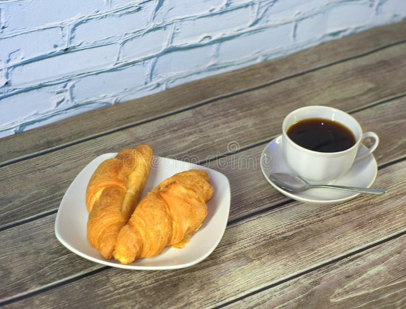 Two freshly baked croissants on a white ceramic plate and a cup of black coffee on a saucer with a spoon on a wooden table against stock images