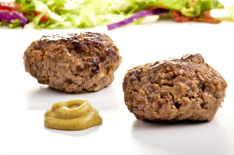 Two freshly grilled meatballs and mustard stock photo