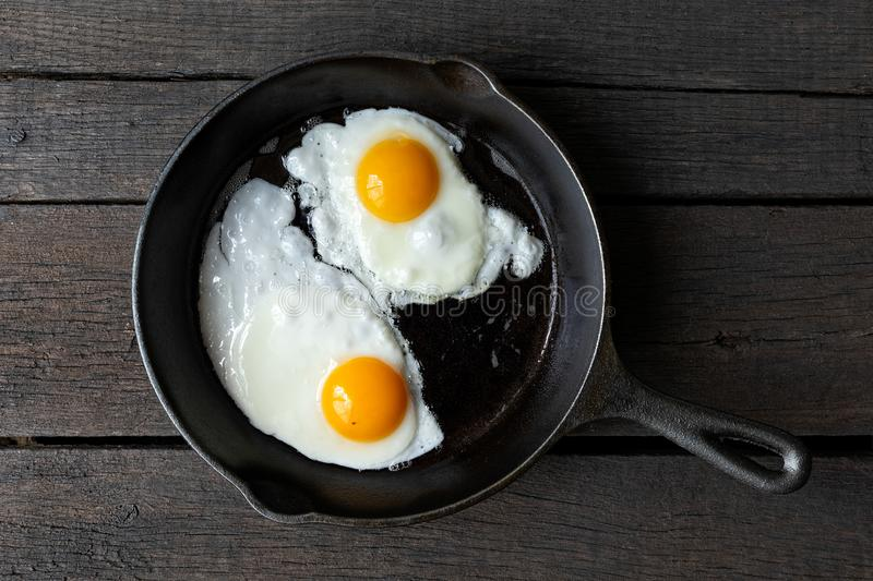 Two fried eggs in cast iron frying pan isolated on dark painted stock photography