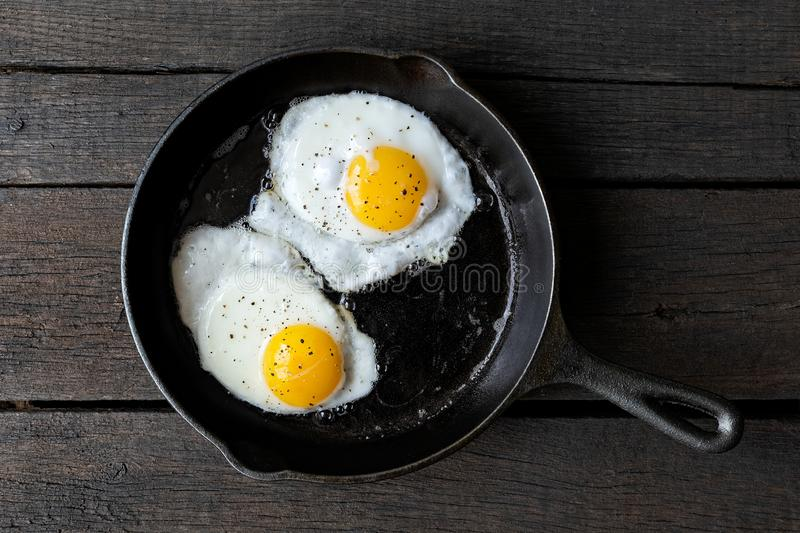 Two fried eggs in cast iron frying pan sprinkled with ground black pepper. Isolated on dark painted wood from above. royalty free stock photo