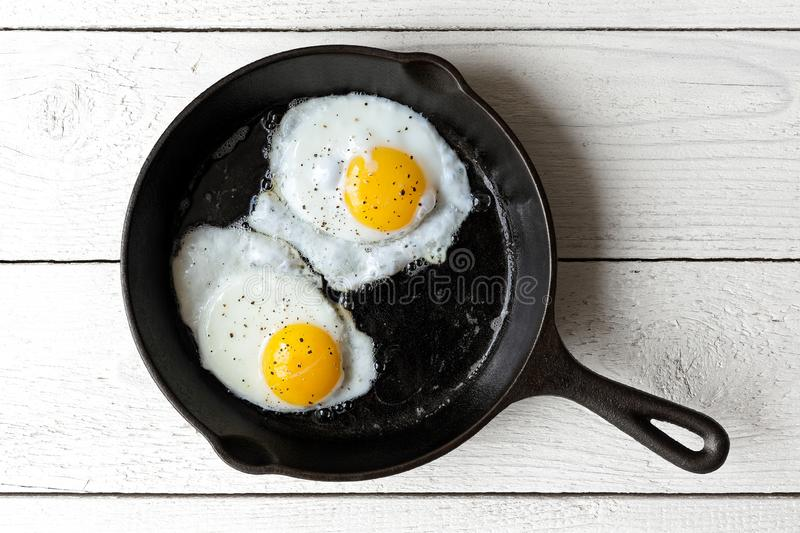 Two fried eggs in cast iron frying pan sprinkled with ground black pepper. Isolated on white painted wood from above. stock photo