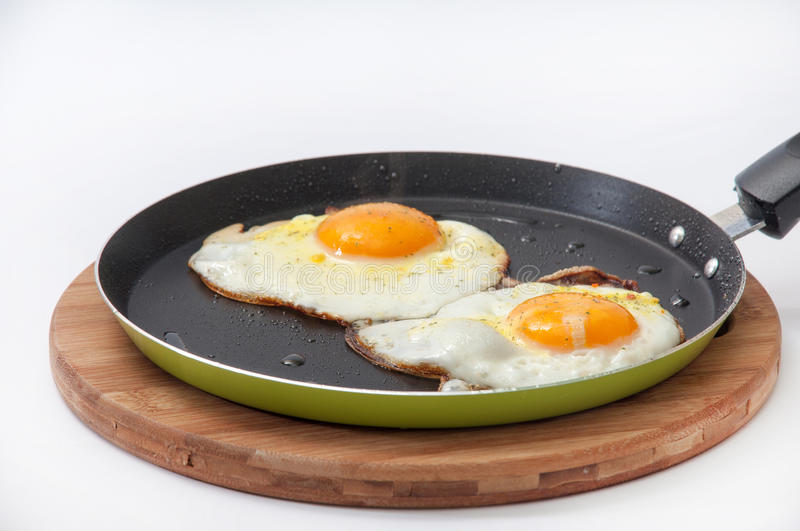 Two fried eggs in a frying pan on a kitchen wooden board.  stock photos