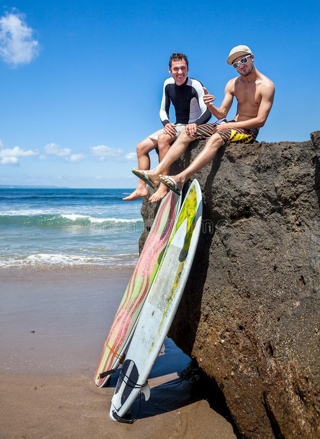 Two friend surfer sitting on rock. Showing sign OK. Two surfboards standing on the sand, leaning on a rocky big stone stock photos