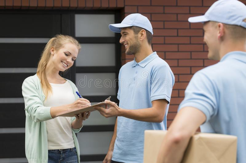 Two friendly couriers and a client stock image