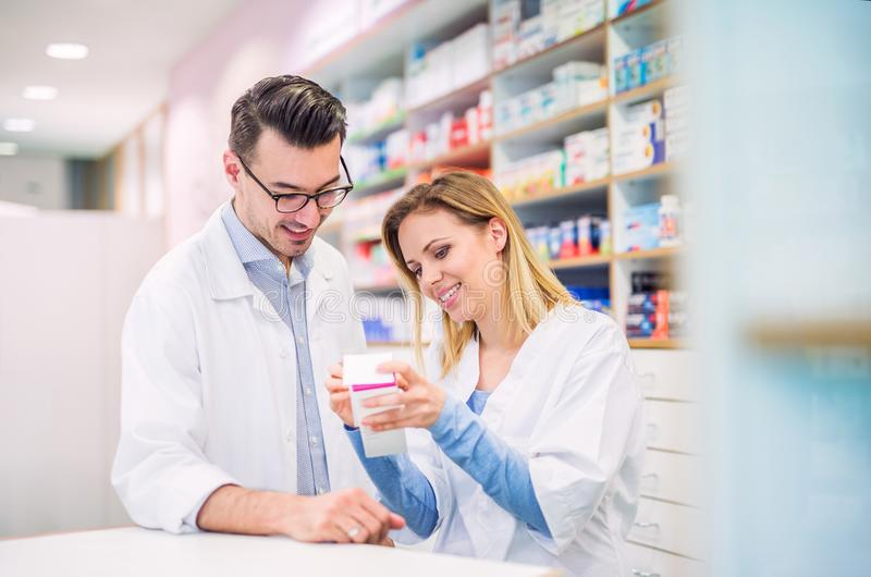 Two pharmacists working in a drugstore. Two friendly pharmacists working in a drugstore royalty free stock photo