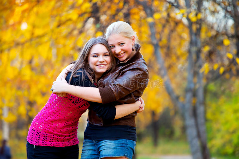 Two friends. Two beautiful teenage girls hugging in the autumn park stock photos