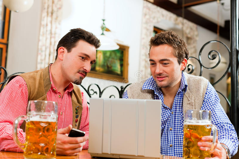Download Two Friends In Bavarian Pub With Laptop Stock Photo - Image of chatting, laptop: 19244554