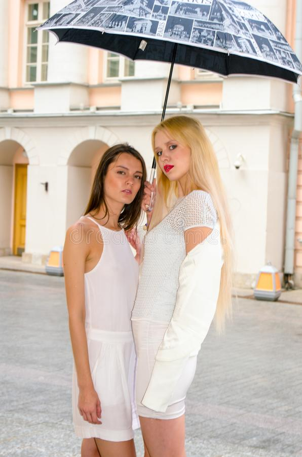 Two friends blonde and brunette in white dresses hiding from the weather under a large umbrella in the alleys of the old city stock photo