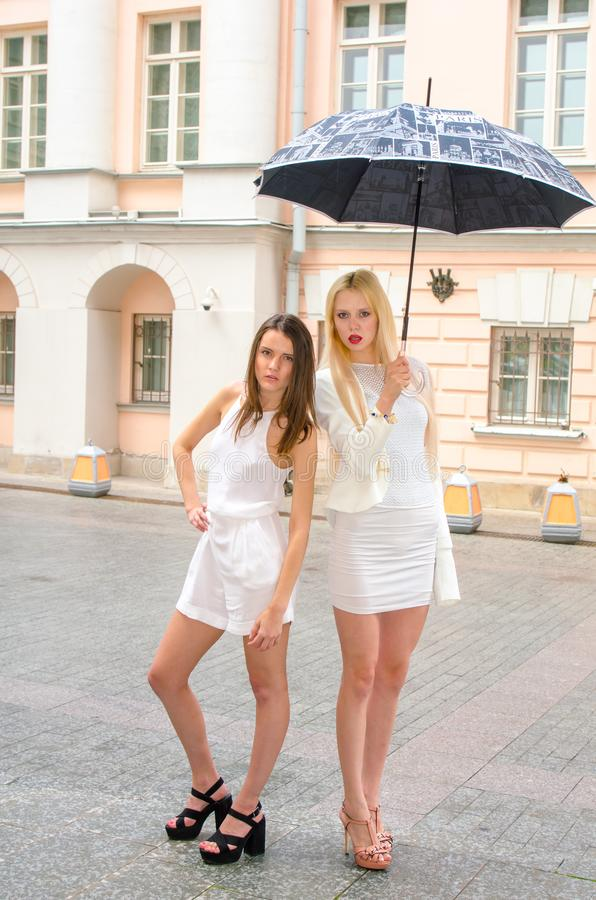 Two friends blonde and brunette in white dresses hiding from the weather under a large umbrella in the alleys of the old city royalty free stock photo