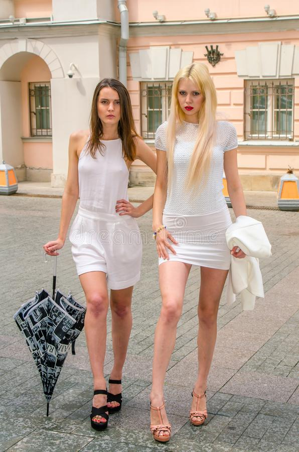 Two friends blonde and brunette in white dresses hiding from the weather under a large umbrella in the alleys of the old city stock images