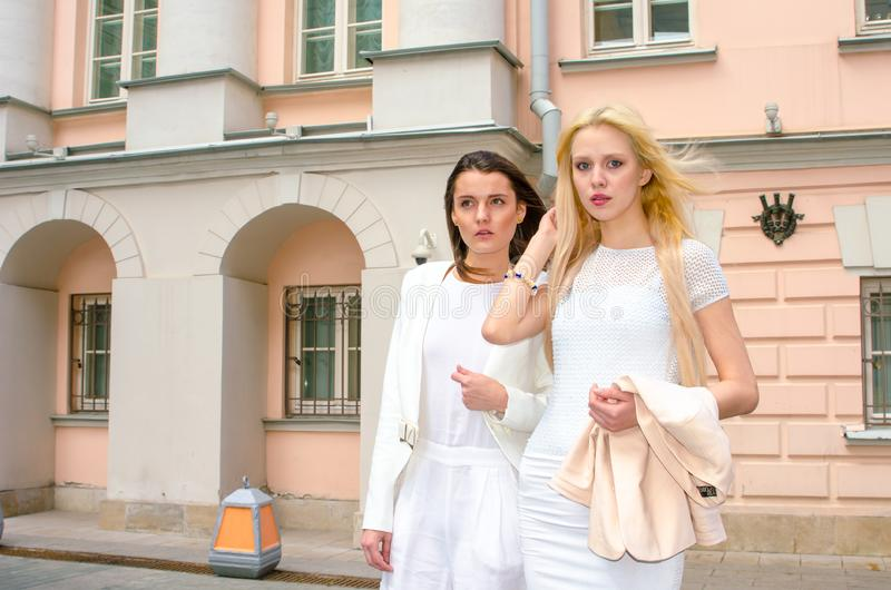 Two friends blonde and brunette in white dresses posing on the street of the old city royalty free stock images