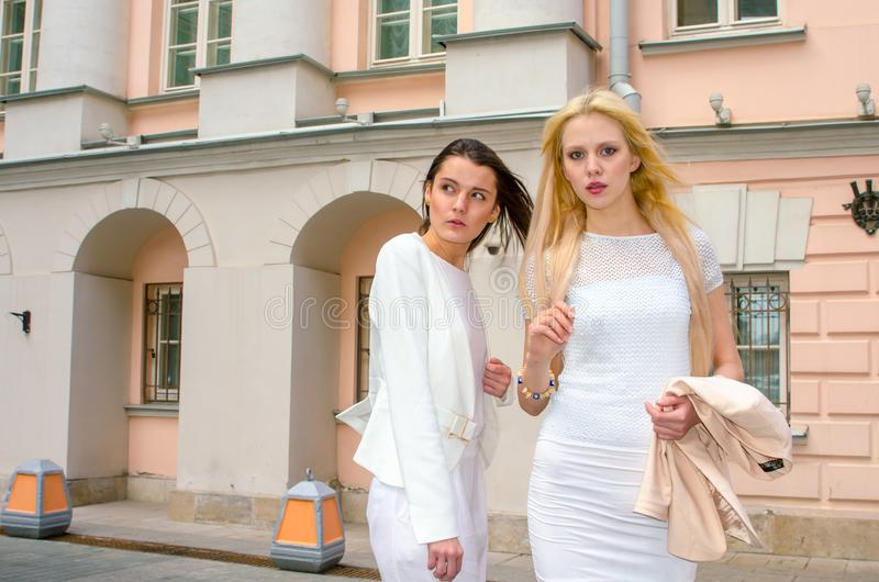 Two friends blonde and brunette in white dresses posing on the street of the old city stock images