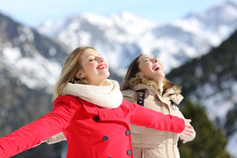 Two friends breathing fresh air in winter in the mountain. Two happy friends breathing fresh air in winter in a snowy mountain royalty free stock photo