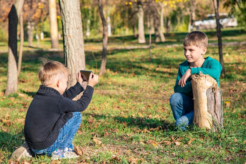 Two friends, brothers are photographed on the phone in the park on a sunny day royalty free stock photography