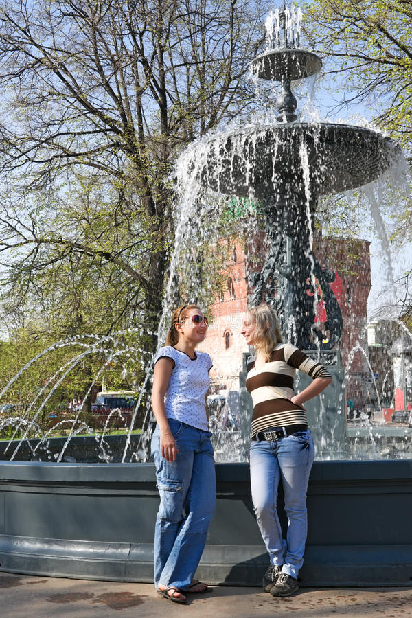 Two friends chatting merrily at the city fountain. The meeting of two friends near the fountain in the city