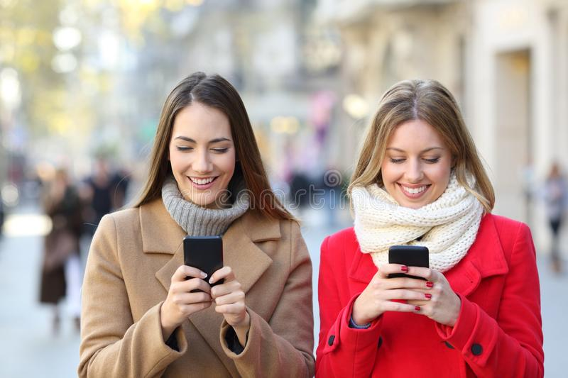 Two friends checking smart phones in the street. Front view of two happy friends checking smart phones in the street in winter stock image