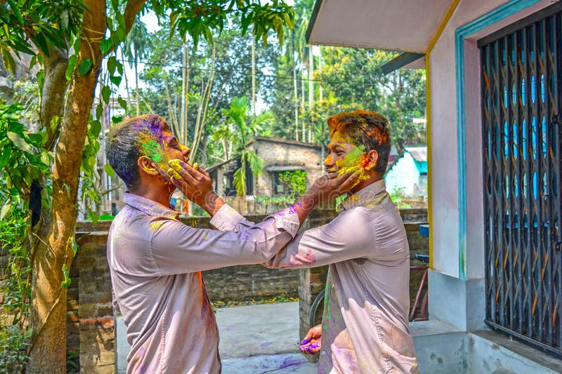 Portrait of two friends are coloring each other during Holi festival in India. royalty free stock image