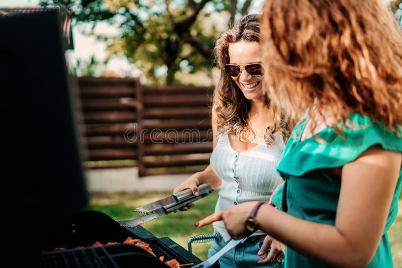 Two female friends cooking on barbeque grill, having lunch in nature with friends royalty free stock image