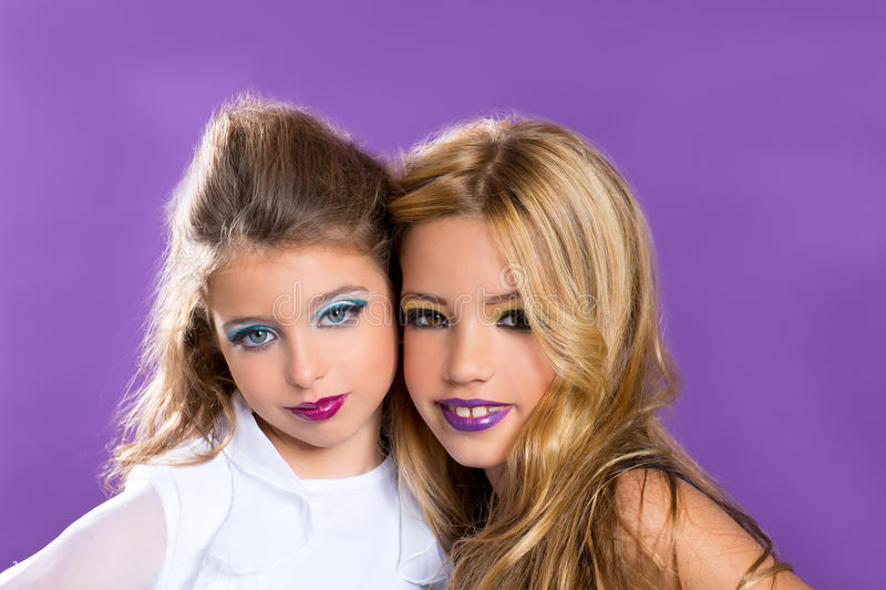 Two friends fashiondoll kid girls with fashion purple makeup stock photography
