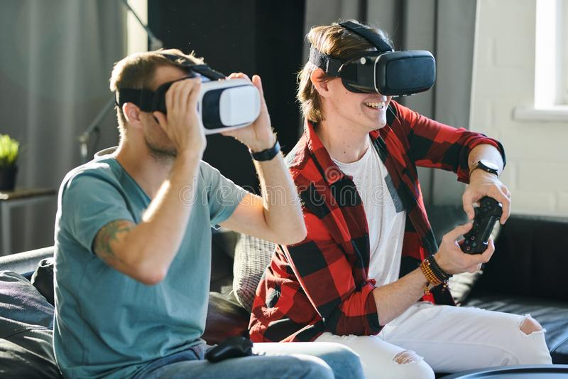 Men playing game with VR device stock photo