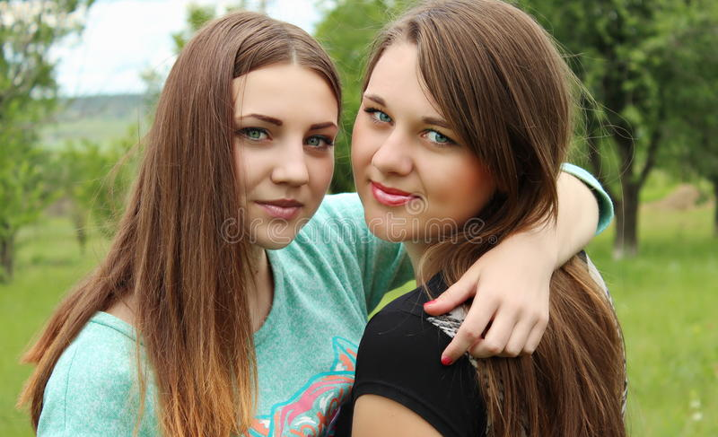 Two friends hugging in the park stock photos