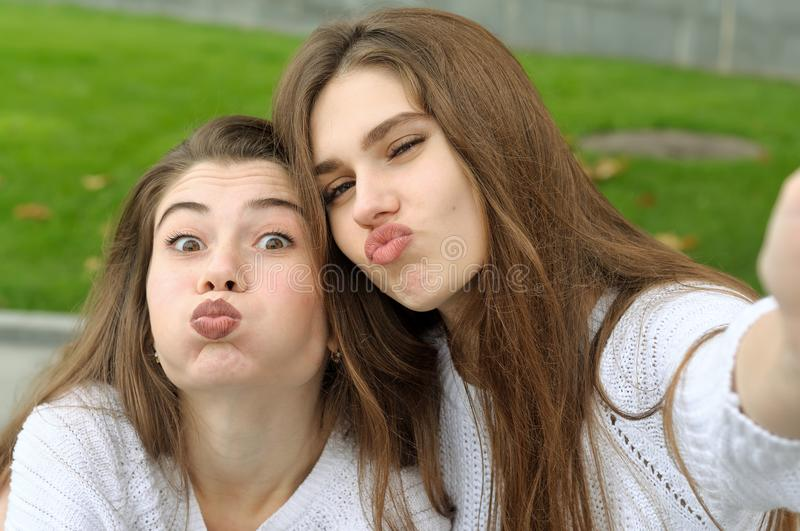 Two friends inflated cheeks while doing selfie photo. They both have long brown hair that is long to the waist and they are dressed in identical white sweaters stock image