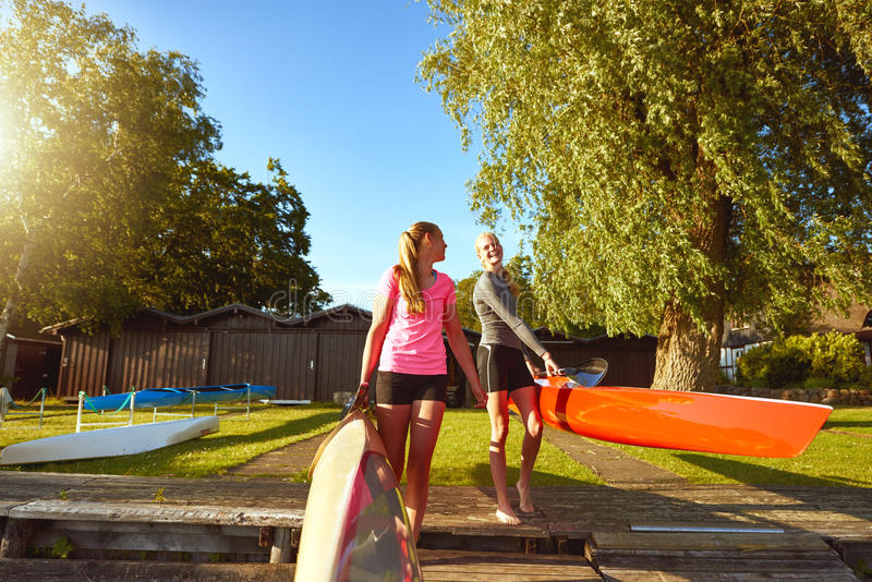 Two friends with kayaks stock images