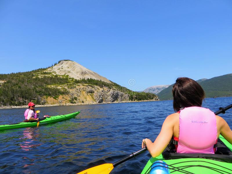 Two friends in kayaks talking and exploring the beautiful waters in Bonne Bay, Gros Morne National Park royalty free stock photo
