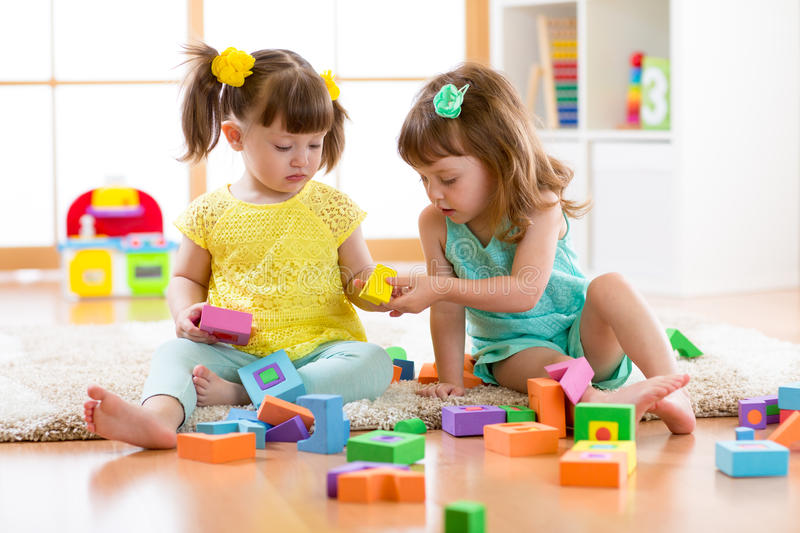 Two friends kids play together in kindergarten, daycare or home. Two friends kids girls play together in kindergarten, daycare or home royalty free stock photography